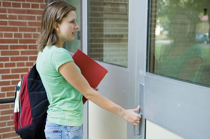 Student with folders opening a door